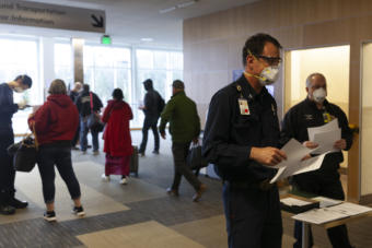 Capital City Fire/Rescue Capt. Roy Johnston talks to people arriving at Juneau International Airport on Saturday, March 21, 2020 in Juneau, Alaska.