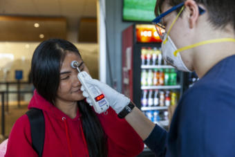 Namfon Noisai gets her temperature checked by Capital City Fire/Rescue's Lily Kincaid during a voluntary screening at Juneau International Airport on Saturday, March 21, 2020 in Juneau, Alaska.