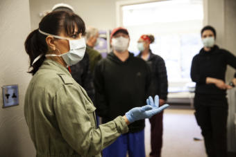 Bartlett Regional Hospital Chief Nursing Officer Rose Lawhorne walks through a newly converted spillover facility designed to house COVID-19 patients on Monday, April 7, 2020 in Juneau, Alaska. The city decided to remove patients from the Rainforest Recovery Center alcohol and drug treatment building and convert it into a facility for non-critical coronavirus patients. (Photo by Rashah McChesney/KTOO)