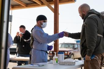 Volunteer Lucas Salzbrun hands out swabs and gives directions on how to do a self-swab at the airport coronavirus test site in Bethel, Alaska on April 29, 2020. (Photo courtesy Katie Basile/KYUK)