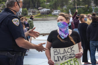 "Juneau Police Department Deputy Chief David Campbell and Borough Assembly member Alicia Hughes-Skandijs talk amid a crowd of about 250 people gathered for a public ""I Can't Breathe"" rally protesting the death of a black man, George Floyd, who was killed after a white officer pressed a knee into his neck while taking him into custody in Minnesota. People held signs decrying violence against black people and calling out institutional racism, many supporting the Black Lives Matter movement on Saturday, May 30, 2020 in Juneau, Alaska. Similar protests happened throughout the state with hundreds turning out in Fairbanks and Anchorage, they've also erupted in dozens of cities all over the country. (Photo by Rashah McChesney/KTOO)"
