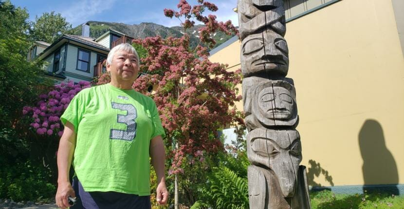 Photographer Brian Wallace poses for a picture next to a totem pole his father, Amos Wallace, carved outside the Juneau-Douglas City Museum in Juneau on June 12, 2020.