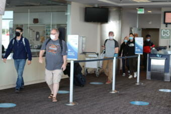 Travelers disembark a plane from Seattle at Ted Stevens Anchorage International Airport
