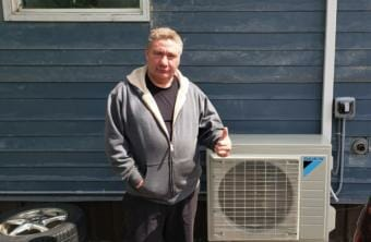 Ray Lindoff poses next to his new air-source heat pump at his home in downtown Juneau on June 5, 2020.