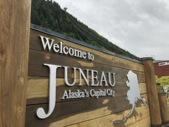 The wood of the Juneau welcome sign on the docks is wet from June rain
