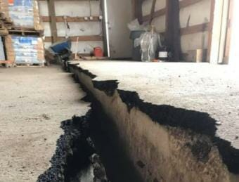 Photo of a large, offset crack in a warehouse floor.