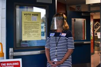 Precinct 20-545 polling chair Sandra Graham, stands outside the polling station in Anchorage on Tuesday morning, Aug. 18, 2020. Among other COVID-19 precautions, volunteers are keeping doors open to limit touch points for voters.