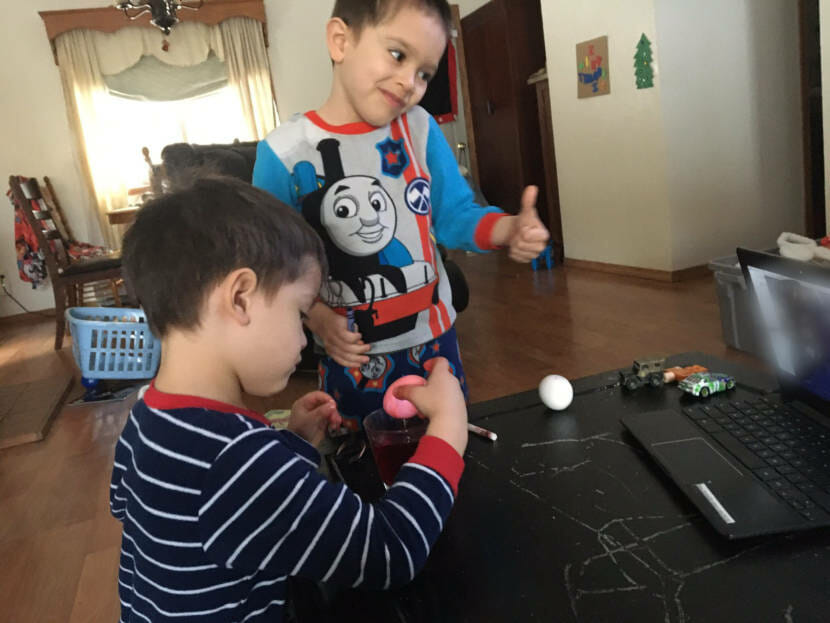 Siblings James Ackerman, left, and Timothy Ackerman, ages 4 and 5, work on Easter eggs at home via distance learning in the spring of 2020.