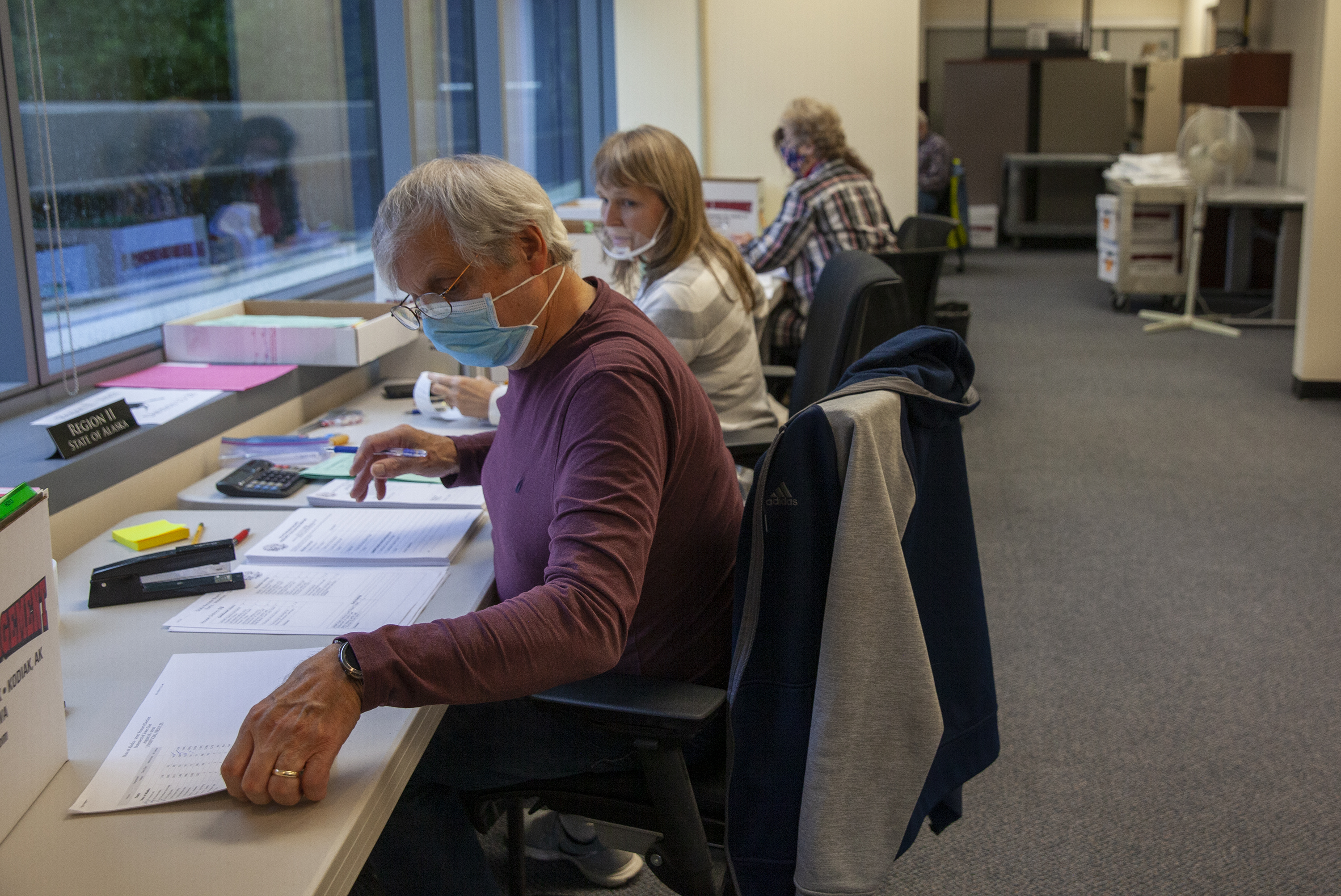 People at the Alaska Division of Elections double-check voter information on August 25, 2020 in Juneau, Alaska. (Photo by Rashah McChesney/KTOO)