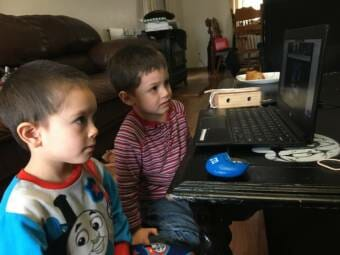 Siblings Timothy Ackerman, left, and James Ackerman, ages 5 and 4, follow classes at home via distance learning in the spring of 2020.