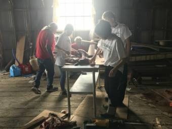 Kake Youth Conservation Corps (YCC) help butcher one of five deer obtained under the emergency season
