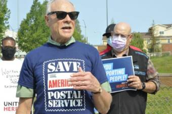 A group of men with signs and shirts supporting the postal service