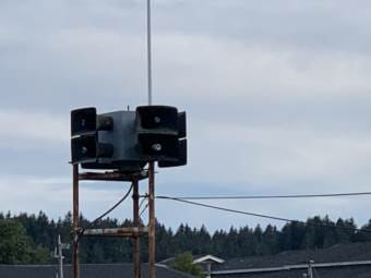 The Kodiak tsunami siren photographed with the sky above it and a tree line below