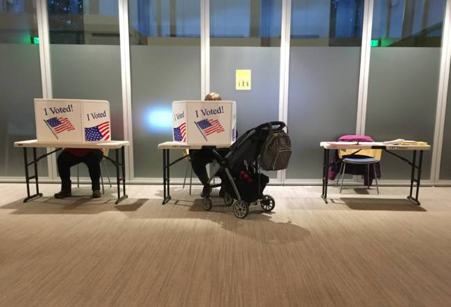 Voters fill out their ballots just an hour before voting was to end in Juneau's municipal elections on Oct. 6, 2020, at Juneau Public Libraries' Valley Branch. Most voters cast their votes by mail, but some went to vote in person. (Photo by Andrew Kitchenman/KTOO and Alaska Public Media)