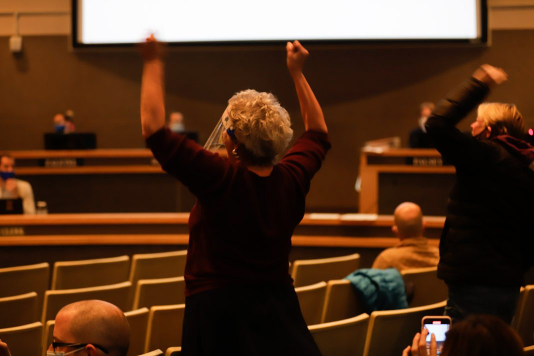 A woman with raised arms during an Anchorage Assembly meeting where Mayor Berkowitz resigned
