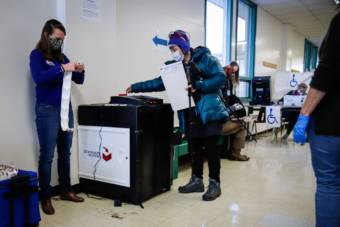 Election workers help a voter at Service High School in Anchorage on November 3, 2020. (Jeff Chen/Alaska Public Media)