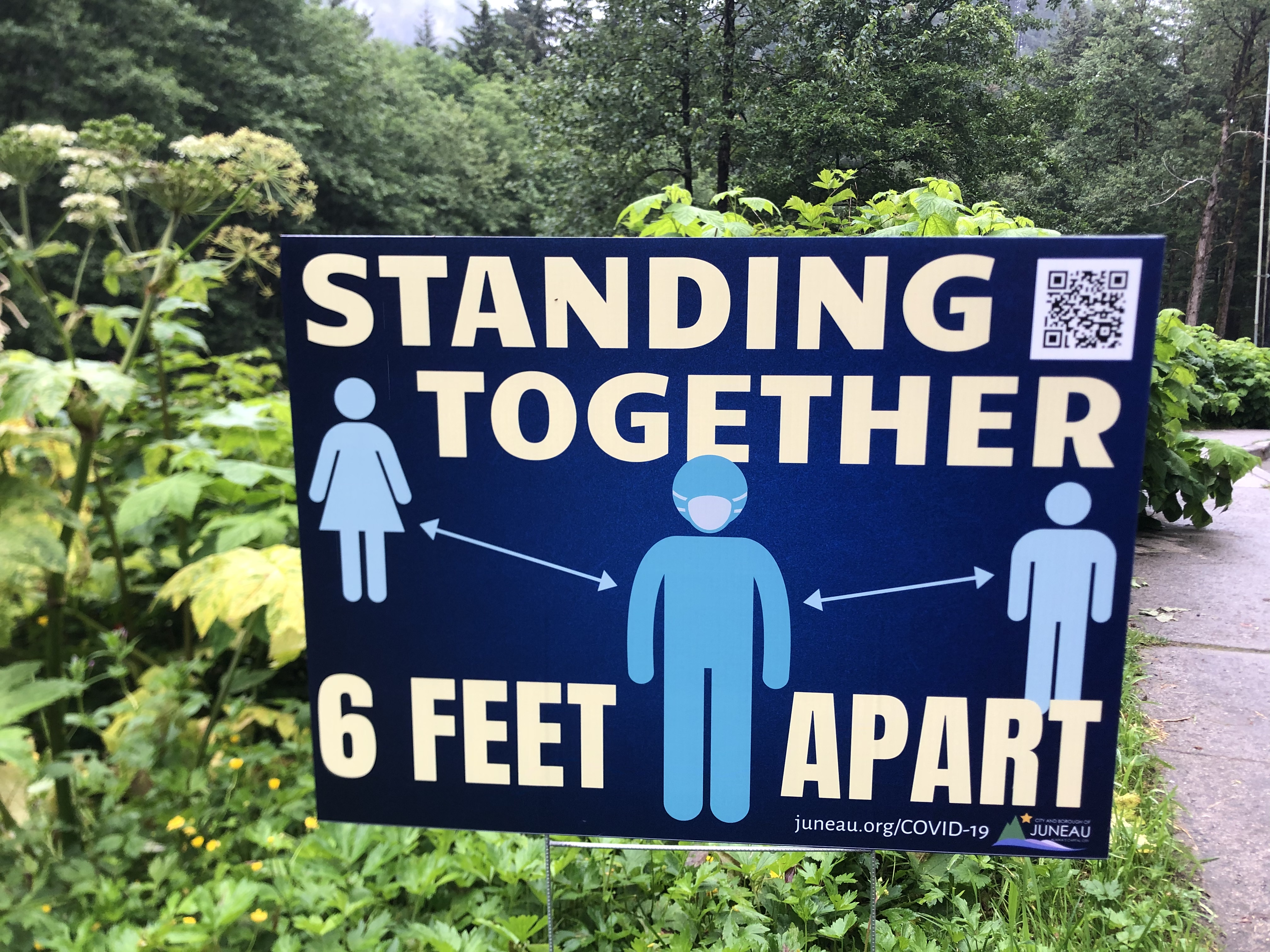 """A sign that says """"Standing Together 6 Feet Apart"""""""