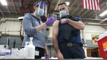 Capital City Fire/Rescue paramedic Lily Kincaid asks Capt. Trevor Richards to verify that there is .3 milliliters of fluid in the syringe with Pfizer's COVID-19 vaccine at the downtown fire station in Juneau on Dec. 17, 2020.