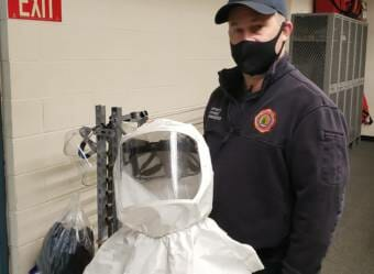 Capital City Fire/Rescue firefighter/paramedic Paul Hammerquist holds a positive air flow respirator, or PAPR, that he wears on certain calls at the downtown fire station in Juneau on Dec. 17, 2020.