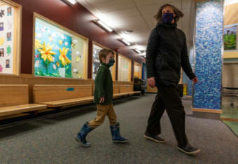 Maxwell Framke, 6, follows Sayéik Gastineau Community School kindergarten teacher Diana Brann on his first day of school on Thursday, Jan. 14, 2021, in Juneau, Alaska. (Photo by Rashah McChesney/KTOO)