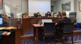 Members of the Senate Health and Social Services Committee hear details about a bill to extend the state's COVID-19 disaster declaration on Feb. 2 in the Capitol. The members, from left, are Sen. Tom Begich, D-Anchorage, behind the plexiglass; Sen. Mia Costello, R-Anchorage; Sen. David Wilson, R-Wasilla; Sen. Shelley Hughes, R-Palmer; Sen. Lora Reinbold, R-Eagle River; and Adam Crum, the commissioner of the Department of Health and Social Services. (Photo by Andrew Kitchenman/KTOO and Alaska Public Media)