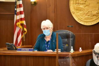 Photo of Alaska House Speaker Louise Stutes as she sits at her bench. She is wearing a disposable facemask and is looking into the House gallery.