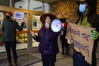 Louise Brady speaks to a crowd of protestors outside of the ADF&G office in Sitka. Brady is a member of the Sitka Tribe of Alaska Tribal Council, but she was speaking as an individual at the event. (KCAW/Berett Wilber)