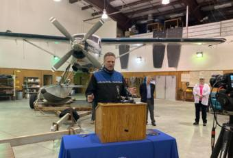 Alaska Gov. Mike Dunleavy speaks about his hopes for holding a summer cruise season this year in a news conference in the hangar of Wings Airways in Juneau, Alaska, on April 9, 2021. Holland America executive Ralph Samuels and Juneau Mayor Beth Weldon are behind Dunleavy. (Photo by Andrew Kitchenman/KTOO and Alaska Public Media)