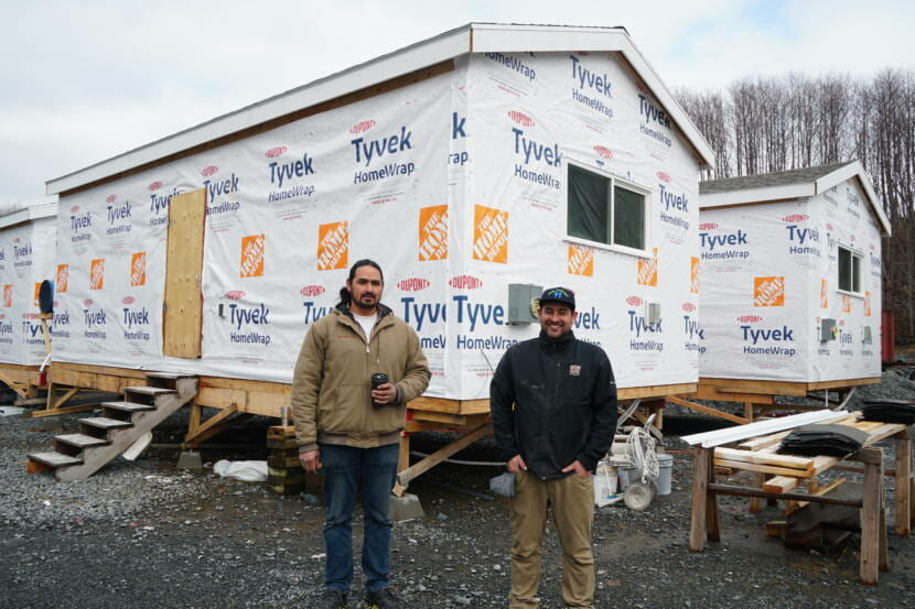 """Co-owners of Sitka Construction Solutions, Derek James and Kris Karsunky, stand in front of the four 450-square foot houses that they're constructing for the Yakutat Tlingit Tribe. The company does standard construction projects like heat pump installs and single family homes, but lately, they've been focusing more on the """"mini home"""" concept. """"We could do these for the rest of our career if we wanted to,"""" James said. """"We saw what we were expecting with the demand, and now we just have to get a process out there."""" (Photo by Erin McKinstry/KCAW)"""