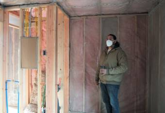 "Co-owner of Sitka Construction Solutions, Derek James, points out the future bathroom in an unfinished ""mini home."" (KCAW/Erin McKinstry)"