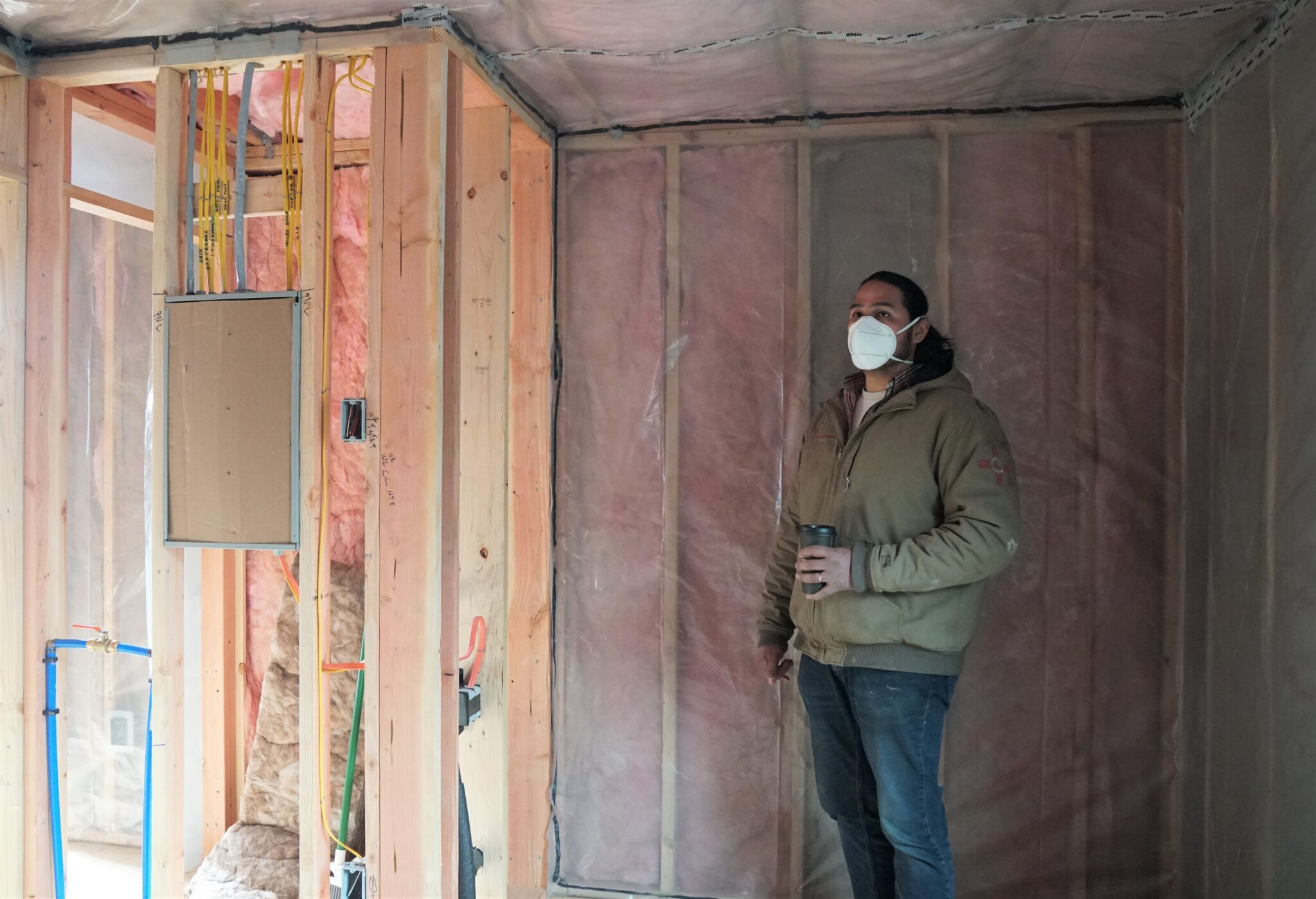 """Co-owner of Sitka Construction Solutions, Derek James, points out the future bathroom in an unfinished """"mini home."""" (KCAW/Erin McKinstry)"""