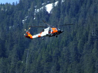 A Coast Guard helicopter hovers over Switzer Creek where the search continues for Geraldine Nelson on Wednesday, May 19, 2021 in Juneau, Alaska. (Photo by Matt Miller/KTOO)