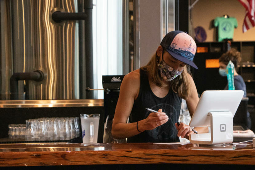 Sara Stekoll works behind the counter at Forbidden Peak Brewery. She is a co-owner of the brewery and asked the City and Borough of Juneau to host a vaccine clinic there.