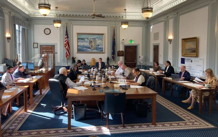 Members of the conference committee on the state budget bills on June 13, 2021, in the Alaska State Capitol in Juneau, Alaska. The bills would fund the budget that begins on July 1, 2021. The members include Reps. Bart LeBon, R-Fairbanks; Kelly Merrick, R-Eagle River; and Neal Foster, D-Nome, seated on the left side of the center table. Sens. Bert Stedman, R-Sitka; Click Bishop, R-Fairbanks; and Donny Olson, D-Golovin, are seated on the left. Chief legislative budget analyst Alexei Painter is seated in the center. Legislative aides are seated around the edges. (Photo by Andrew Kitchenman/KTOO and Alaska Public Media)