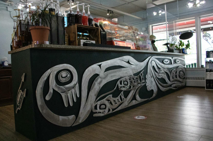 An aluminum carving created by Tlingit artist Robert Mills is mounted below the bar counter at the Sacred Grounds coffee shop in Juneau, Alaska. (Photo by Lyndsey Brollini/KTOO)