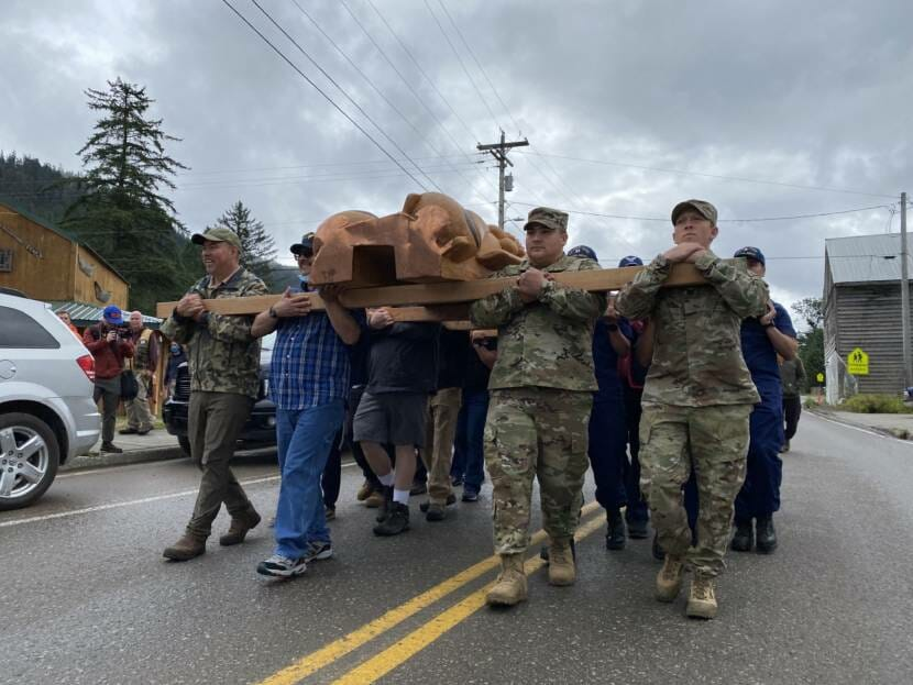 Veterans carry a totem pole to its permanent location in Hoonah. The pole was raised during a ceremony on Saturday July 24.