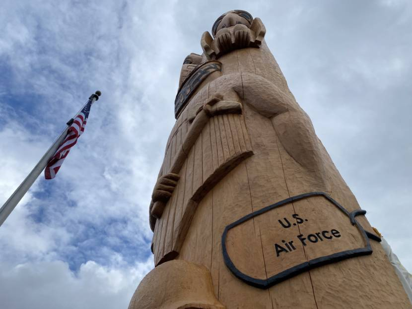 Toward the middle of the totem pole are carved dog tags representing each branch of the service, including the Alaska Territorial Guard, and a Tlingit warrior dressed in armor.