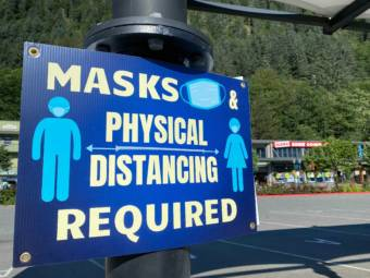 """A blue sign with off white lettering that says: """"Masks & physical distancing required"""" in all capital letters."""