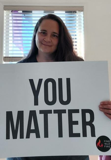 Juneau resident Casey DenAdel poses with a 'you matter' sign she displays in her window.