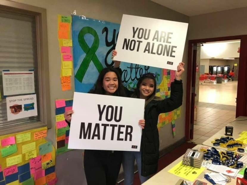 Two Juneau high school students pose with signs displaying positive messages during a 'Take a Time Out to Talk' event in 2020.