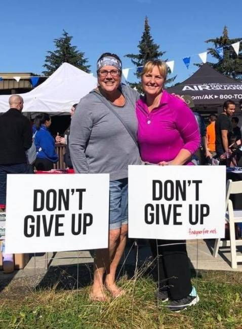 Timi Tullis and Melissa McCormick pose with 'don't give up' signs during an event at the University of Alaska Southeast.
