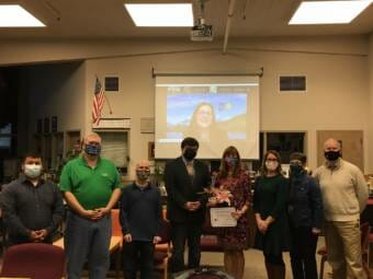 Juneau School District Superintendent Bridget Weiss poses with school board members during a meeting on Tuesday, Sept. 14, 2021. Lisa Parady with the Alaska Superintendents Association showed up via Zoom to present Weiss with an award.