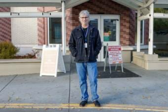 A doctor standing at the entrance to the Alaska Native Medical Center in Anchorage