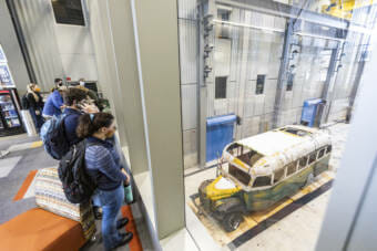 Students looking down on the Chris McCandless bus in a high-ceilinged vehicle bay