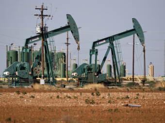 A green pump jack in a Texas oilfield