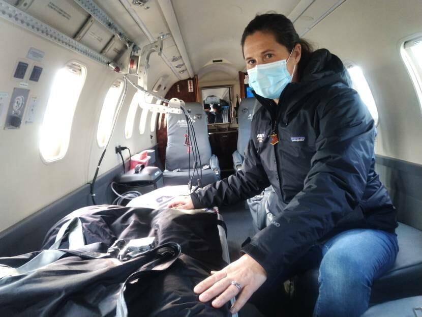A woman inside a medevac lear jet, next to a stretcher